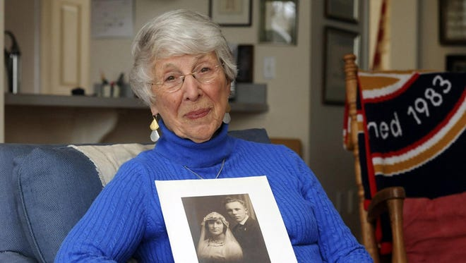 Lucy Duffy of Brewster holds the wedding photo of her parents, Charles DeVries and Rebecca Goethe DeVries, who met in France during World War I. He was an American soldier and she was a French hospital worker.