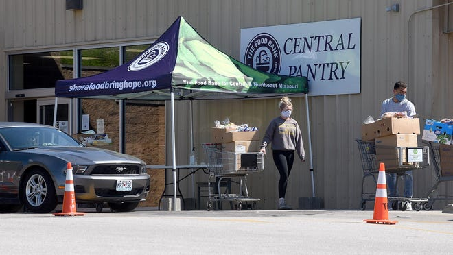Central Food Pantry workers bring out food in April after the pantry switched to drive-through distribution in response to the COVID-19 pandemic. Hours will be reduced at the pantry at 1007 Big Bear Blvd. to enhance staff safety and efficiency.