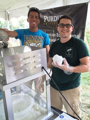 Native Hawaiian Purdue students Dairius Kawewehi (left) and Kyle Dahlin serve Hawaiian shave ice during the Native American Educational and Cultural Center's open house in August.