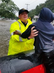 A Bossier Parish deputy helps evacuate a child from a flooded home