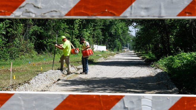 Surveyors  Mark Toth, left, and Spencer Wright mark the offset for the curbing as they work on the Hi-Rail Greenway Passage extension under construction along U.S. 41 near Taylor Avenue in Evansville Friday. The $2,253,300 project involves constructing a 10-foot wide bicycle and pedestrian trail along the former Hi-Rail railroad bed on the west side of US 41 from Riverside Drive to Walnut Street, June 29, 2018.