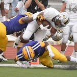 Calvary's Orlando Bradford is hit by a pair of Byrd defenders during second quarter action of their game in September.