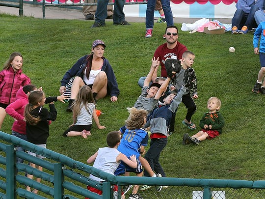 Young fans at Frontier Field chase a foul ball along the grassy area in right field.