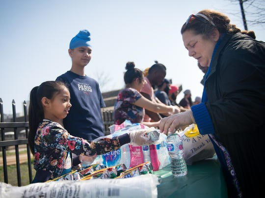 Nimmer Kaur, 7, of Cinnaminson, hands juice to Dina Bova, of Camden, on Martin Luther King Blvd. in Camden, N.J. on Saturday, April 14, 2018. Volunteers from the Sikh Coalition come from throughout Pennsylvania and New Jersey to distribute food and clothing at this location every month.