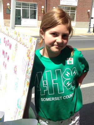 In this May 9, 2015 photo, 12-year-old Megan Parkinson tends a trivia booth for the Somerset County 4-H at Street Fest in historic downtown Princess Anne. Megan attends Somerset Intermediate School in Westover. The annual Mother's Day weekend event attracted hundreds.