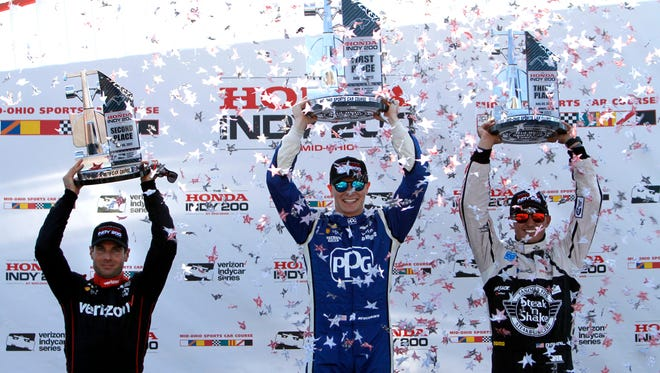 Second-place finisher Will Power, right, winner Josef Newgarden, center, and third-place finisher Graham Rahal raise their trophies in Victory Lane at the IndyCar Honda Indy 200 auto race Sunday, July 30, 2017, at Mid-Ohio Sports Car Course in Lexington, Ohio. (AP Photo/Tom E. Puskar)