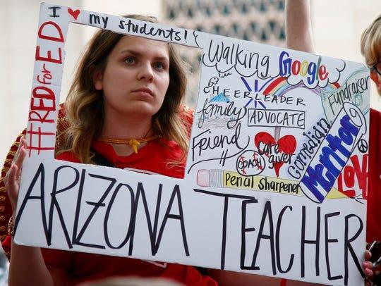 Teacher Taylor Dutro listens as protest organizers