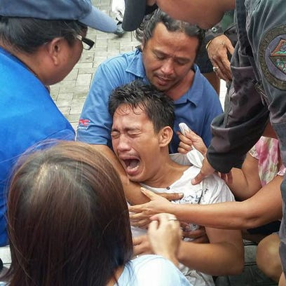 A survivor of a passenger ferry that capsized in rough waters cries after arriving at the pier in Ormoc City, central Philippines on July 2, 2015.