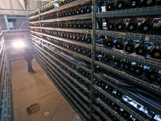 Workers look over racks of Bitcoin data miners during