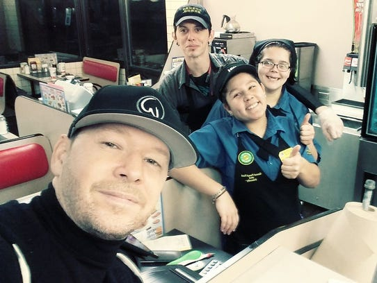 Donnie Wahlberg takes a selfie with employees at an