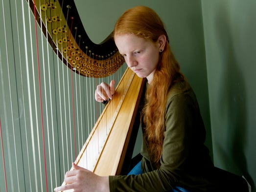 Amy Carty plays her harp at her home in Lenoir City,