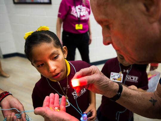 Angie Sanchez, 8, watches in awe as Dick Grace, of Grace Family Vineyards, performs a magic trick for her during the Naples Winter Wine Festival's Meet the Kids Day at the Boys & Girls Club of Collier County in Naples on Friday, Jan. 26, 2018.