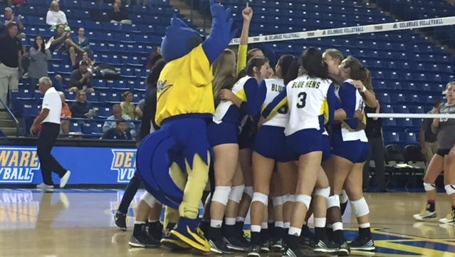 Delaware volleyball players, joined by mascot YoUDee, swarm the Carpenter Center floor to celebrate Friday night's 3-0 win over William & Mary.