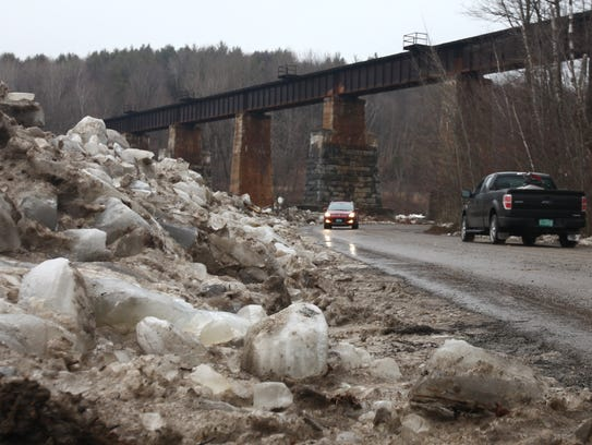 Ice from the Lamoille River is cleared to the side