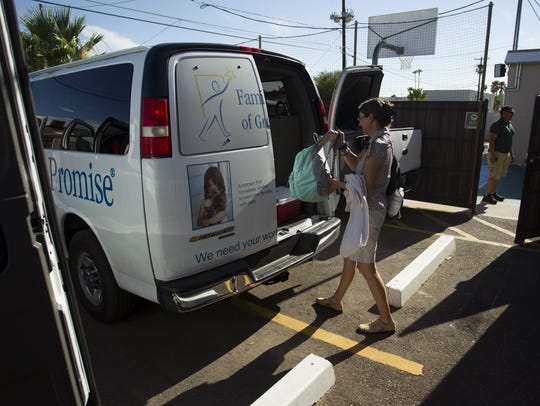 A woman loads her belongings into a van at Family Promise