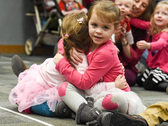 Kids pass out hugs during the Valentine's Day party on Wednesday, Feb. 14, 2018 at the West Des Moines Library.