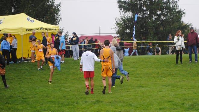 Laingsburg runner Ryan Kingsbury, left, helped ailing Pewamo-Westphalia runner Trent Barker, gold uniform, back to his team tent following the Greater Lansing cross country championships.