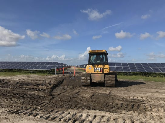 A worker prepares the ground for more solar panels at Florida Power & Light's Indian River solar-energy center near Vero Beach, Florida, on Oct. 10, 2017. FPL is nearly tripling its solar-powered portfolio with the eight sites it has under construction, but the state still falls far short of other sunny locales for solar usage.