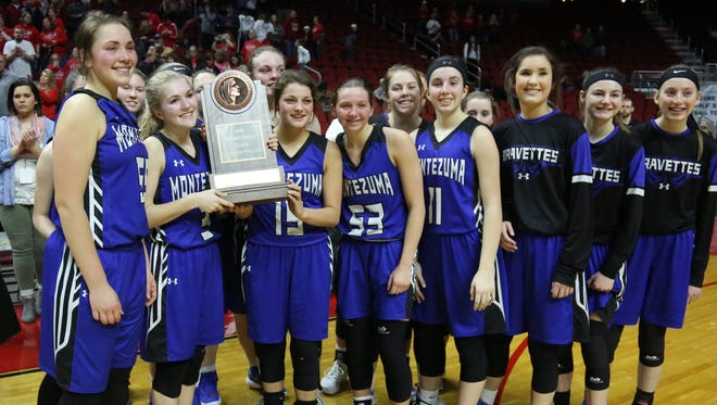 The Montezuma Bravettes hold on to the 2018 Class 1A State Basketball Tournament participation trophy they received after their 52-48 loss to Central Decatur at Wells Fargo Arena in Des Moines.