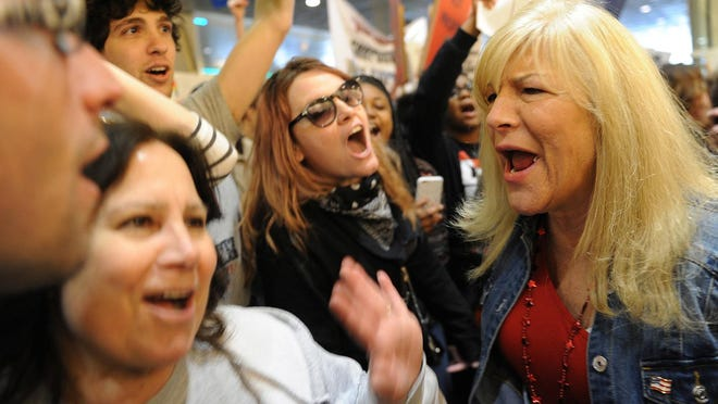 Judy Stabile of Oakmont, Pa., left, confronts anti-Trump protesters as she waits in line to enter the David L. Lawrence Convention Center for a rally for Republican presidential candidate Donald Trump in Pittsburgh, Wednesday, April 13, 2016.