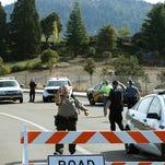 Officers direct traffic on a road leading to the Umpqua Community College campus in Roseburg, Ore., after a deadly shooting Thursday, Oct. 1, 2015. (Chris Pietsch/The Register-Guard via AP) MANDATORY CREDIT