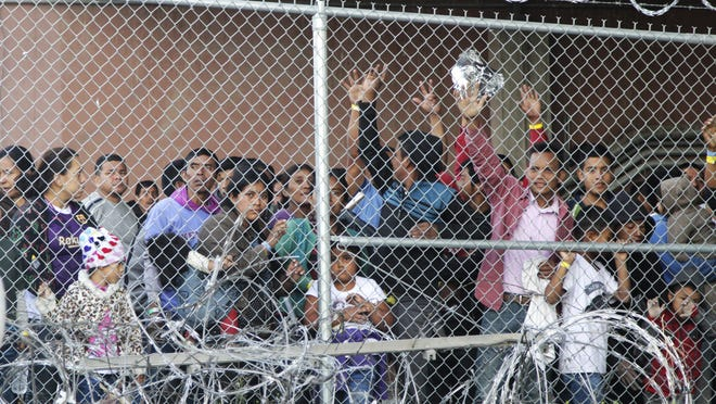In this March 27, 2019, file photo, Central American migrants wait for food in a pen erected by U.S. Customs and Border Protection to process a surge of migrant families and unaccompanied minors in El Paso, Texas. A federal advisory group is calling for significant changes to how the federal government deals with the surge of migrant families that officials say is overwhelming the southern border.