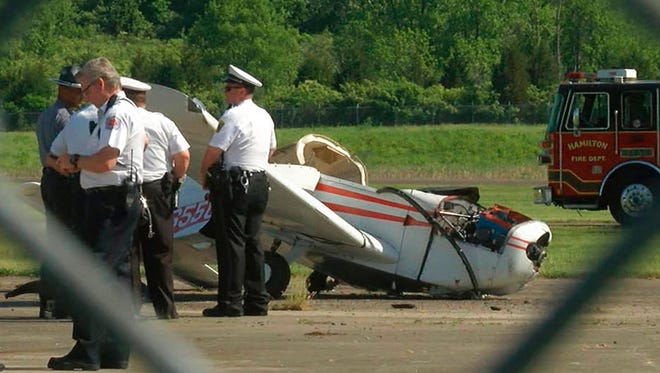 In this frame from video, police investigate a plane crash at the Butler County Regional Airport on Tuesday, May 15, 2018, in Hamilton, Ohio. The pilot of a single-engine plane that crashed during takeoff has been flown by helicopter to a Cincinnati hospital to be treated for injuries.