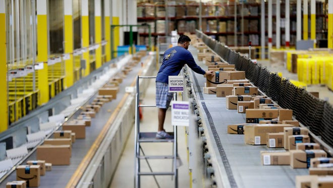 In this 2017 photo, an Amazon employee makes sure a box riding on a belt is not sticking out at the Amazon Fulfillment center in Robbinsville Township.