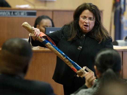 In the foreground, Charlie Bothuell IV, left, and Monique Dillard-Bothuell, sit in court today as Assistant Wayne County Prosecutor Carin Goldfarb prepares to hand a police witness a PVC pipe that was allegedly used to beat Bothuell's son.