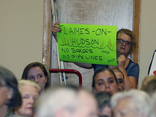 A women holds a sign during a public hearing about