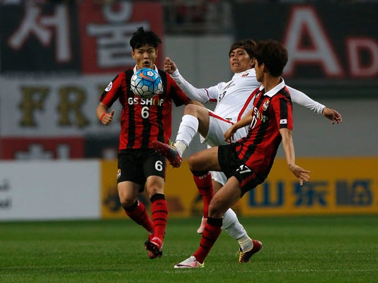 Yosuke Kashiwagi of Japan's Urawa Reds, center, fights for the ball against South Korea's FC Seoul Ju Se-jong, left, and Yun Il-lok, right, during the second leg of their Asian Champions League Round of 16 soccer match at Seoul World Cup Stadium in Seoul, South Korea, Wednesday, May 25, 2016. (AP Photo/Lee Jin-man)
