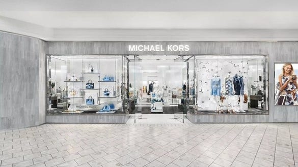 Michael Kors storefront with gray walls, white tile floor, and off-white ceiling.