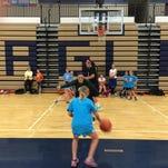 MSU junior Tori Jankoska demonstrates shooring form before a drill at Hartland's girls basketball camp on Wednesday.