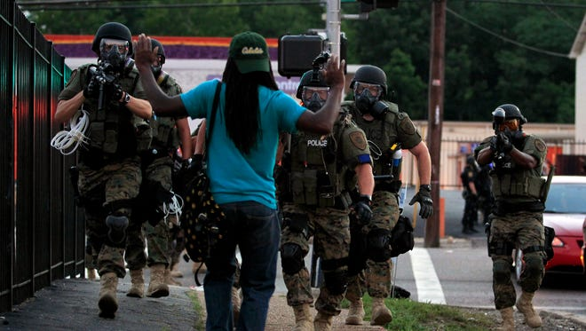 Police wearing riot gear walk toward a man with his hands raised in Ferguson, Mo.