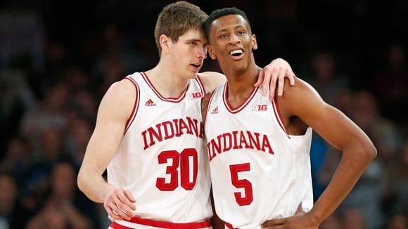 Indiana forward Collin Hartman (30) consoles forward Troy Williams (5) after Williams drew a foul call in the second half of an NCAA college basketball game against Georgetown at Madison Square Garden in New York, Saturday, Dec. 27, 2014. Georgetown defeated Indiana 91-87 in overtime. (AP Photo/Kathy Willens)
