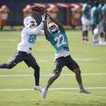 Dolphins cornerback Jamar Taylor (22) breaks up a pass intended for wide receiver Greg Jennings (85) during training camp Thursday in Davie. It was the first practice for a particularly upbeat Miami team this season.