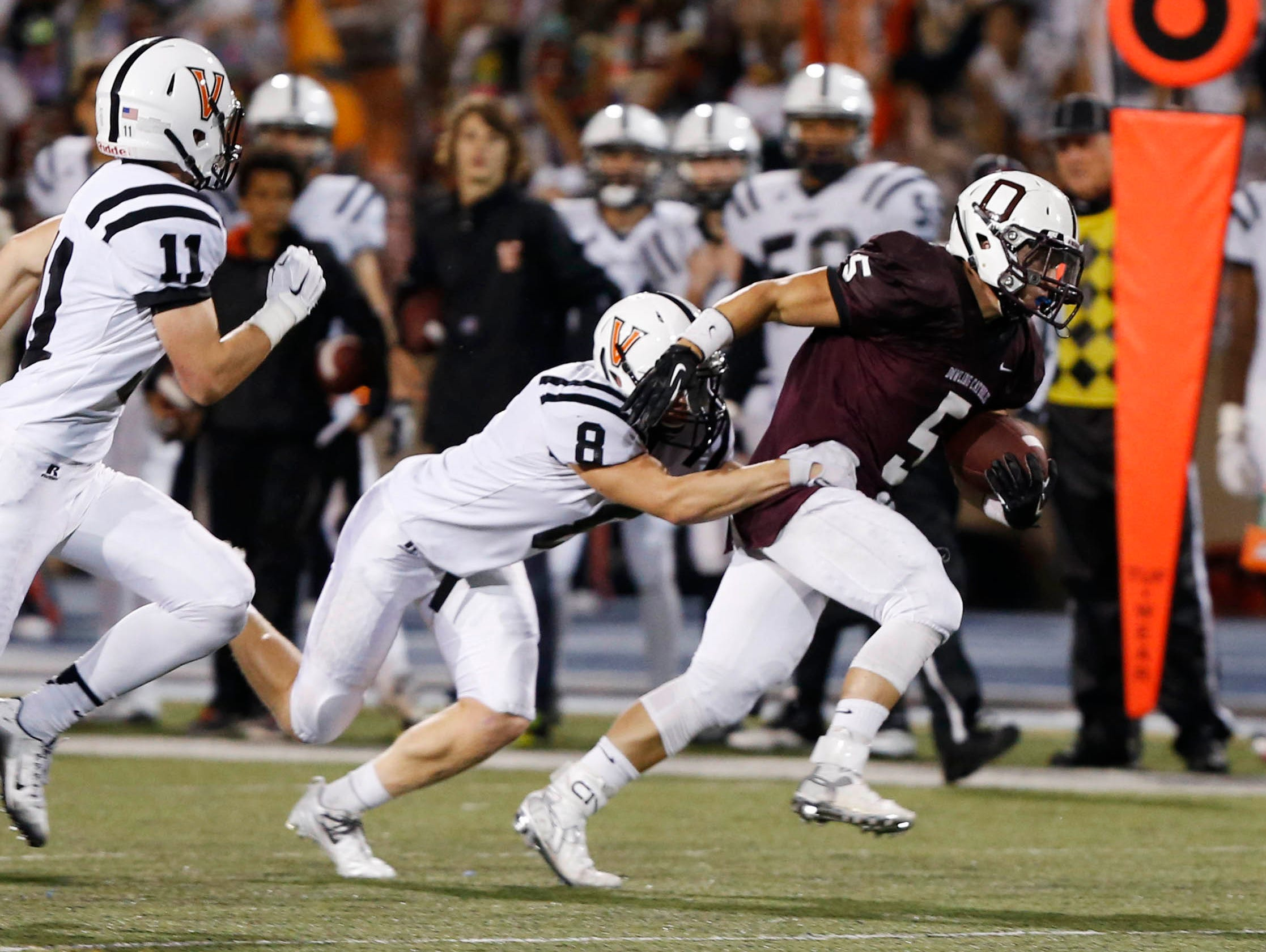 Dowling Catholic's Cole Deskin (5) tries to break away from Valley's William Phillips (8) Friday, Sept. 18, 2015, at Drake Stadium in Des Moines.