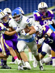 Catholic Central's Cameron Ryan (with ball) tries to