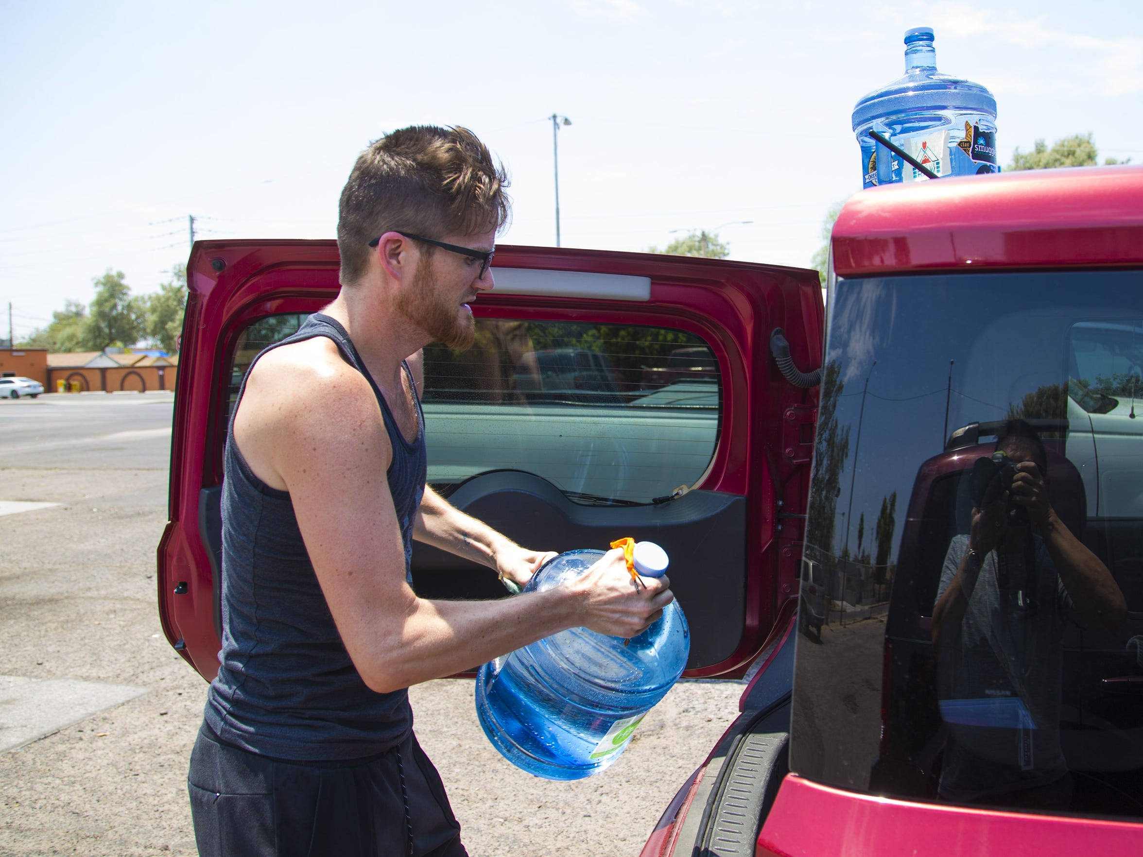Tyler Hurst loads water into his car at a water station in Phoenix on June 20, the hottest day of 2017.