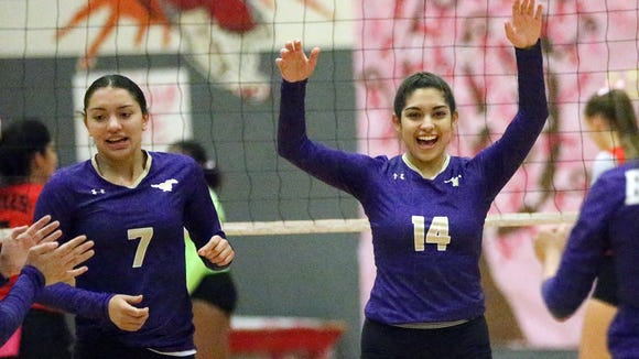 Andrea Gandarilla, 14, and Savannah Marenco, 7, celebrate a point against Jefferson Tuesday night. The visiting Mustangs prevailed over the Foxes in three sets.