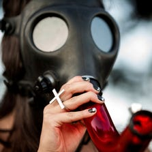 In this Sunday, Aug. 17, 2014 photo, a young woman enjoys the enveloping high of a mask bong on the final day of Hempfest, Seattle's annual gathering to advocate the decriminalization of marijuana, at Myrtle Edwards Park on the Seattle waterfront. Legalization of recreational pot has left states wondering whether there will be more fatal marijuana-related crashes.