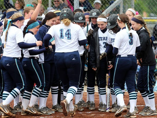 Siegel players gather around home plate to greet teammate