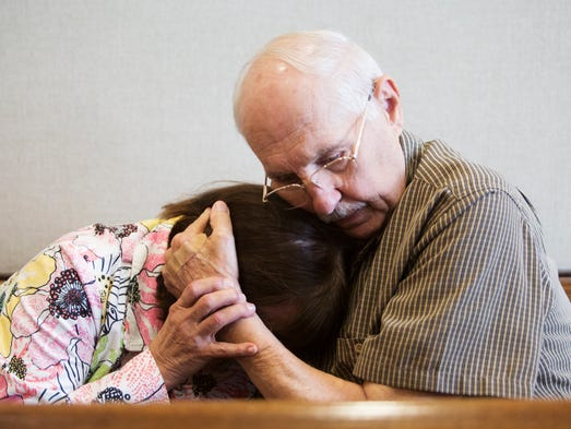 Mary Ann Groves is comforted by her husband, Tom, after