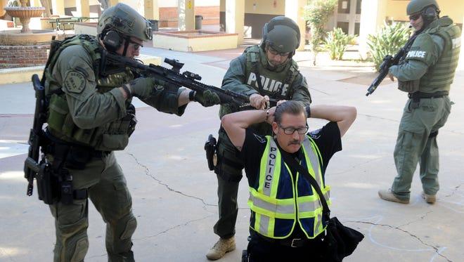 From left, Chad Peplinski, Ramzi Raad and Jeremy Watson arrest simulated  gunman John Brockus on Thursday at Santa Paula High School.