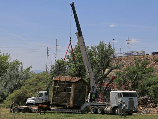 The old Silver Reef jail is loaded onto a trailer Tuesday