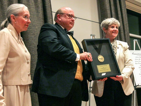Julie Barton, left, and Carol Burdette, right, both of United Way of Anderson County, present Evans Whitaker with the 2016 Communitarian Award during a ceremony held at Anderson University on Thursday.