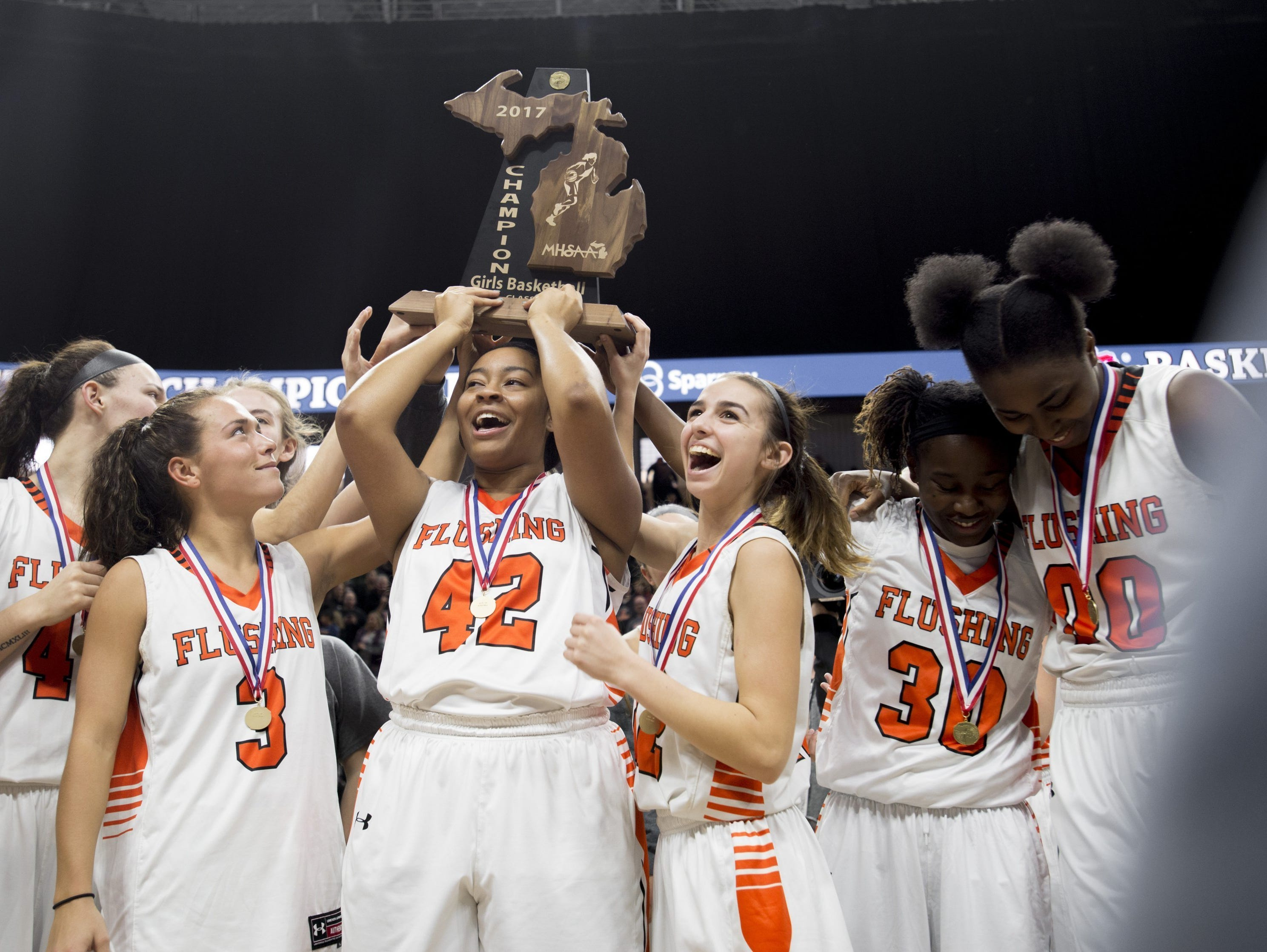 Flushing players hold up their Class A state champion trophy after winning, 49-38, over East Kentwood in East Lansing on March 18, 2017.