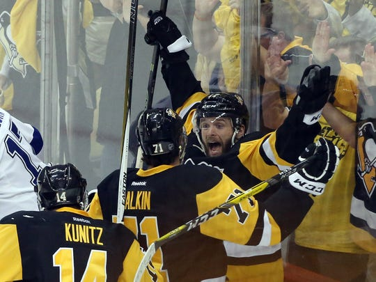 Pittsburgh Penguins teammates celebrate after scoring