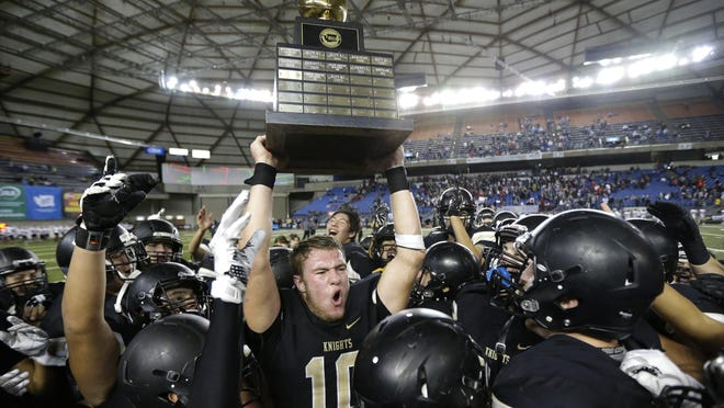 In this Dec. 3, 2016 file photo, Royal quarterback Kaden Jenks (10) celebrates with the trophy after Royal beat Connell in the Washington Div. 1A high school football championship in Tacoma, Wash. The overwhelming uncertainty of whether high school sports can go forward in the fall of 2020 amidst the continued COVID-19 pandemic is a constant refrain among administrators and decision makers as the clock ticks closer to the start of the 2020-21 school year with little clarity in place for an obvious and safe path moving forward for athletics.