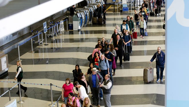 A long line of travelers waits to pass through the TSA check point at O'Hare International Airport in Chicago.